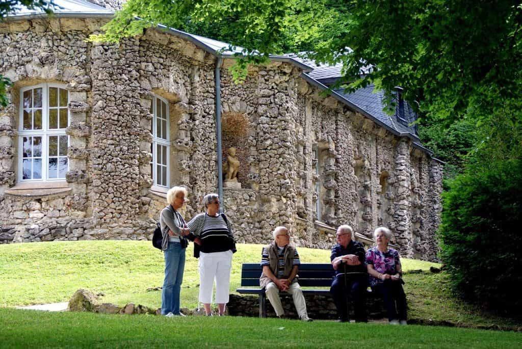 Grupo de idosos se reúne em banco de jardim.