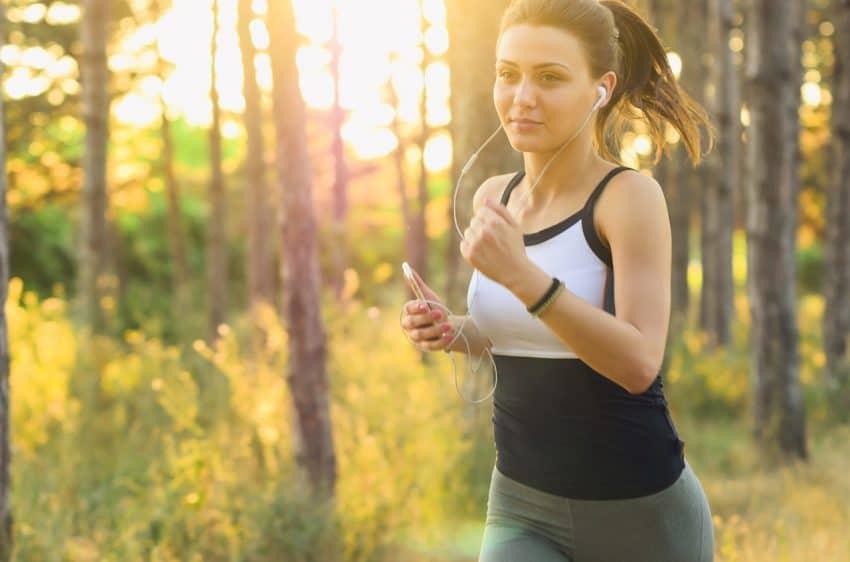 Mulher correndo no parque, com fone de ouvido e celular na mão.