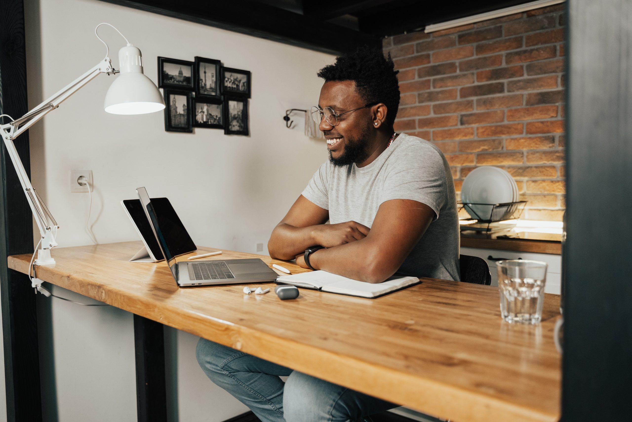 Na foto um homem sorrindo sentado em uma mesa olhando para um notebook.