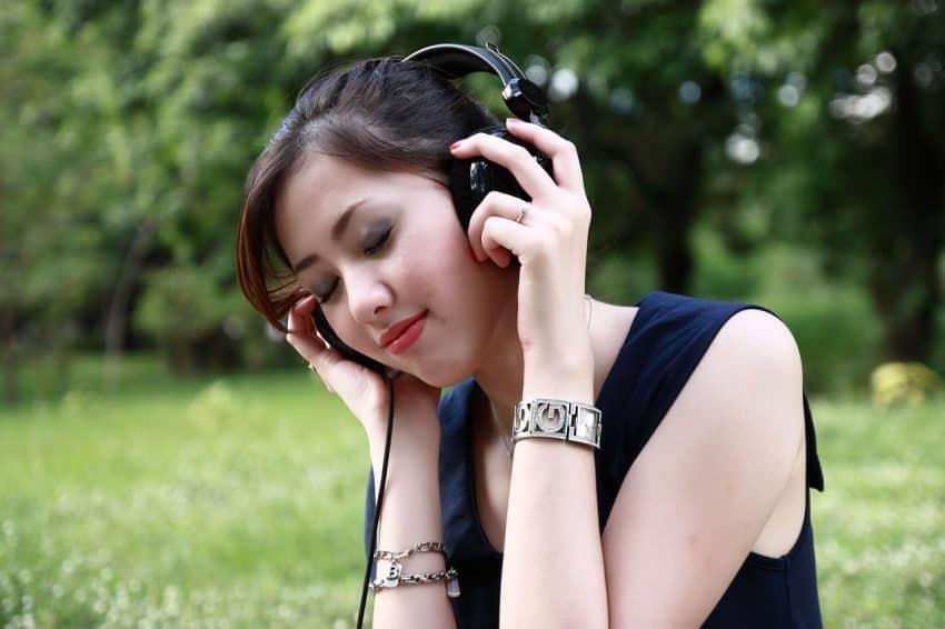 Mulher com fone de ouvido grande no parque.