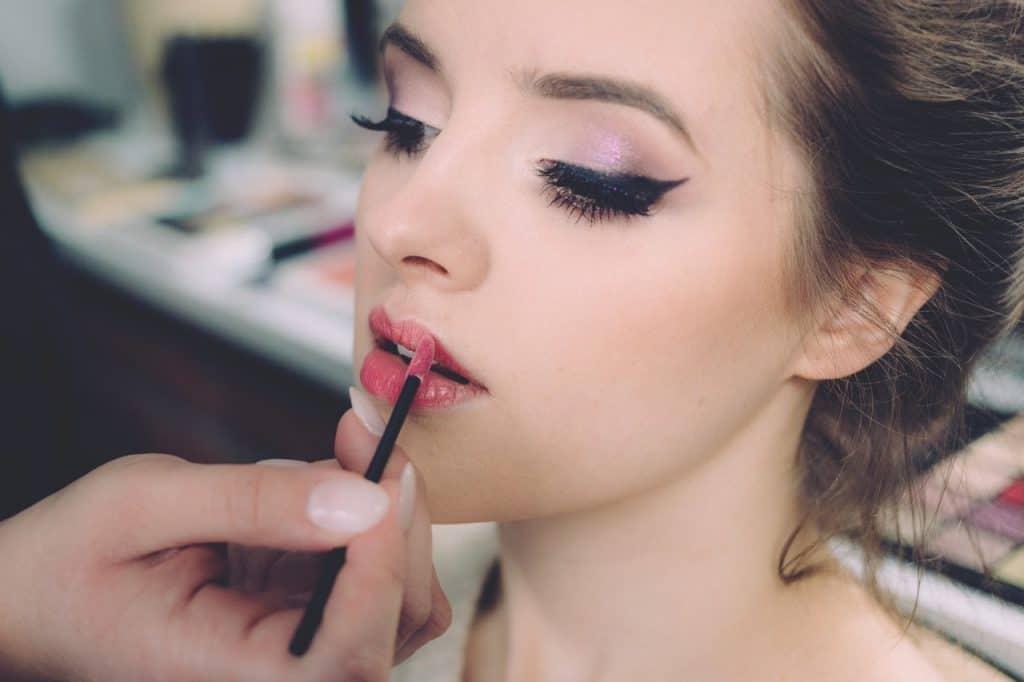 Imagem de uma mulher sendo maquiada, maquiadora está passando gloss.
