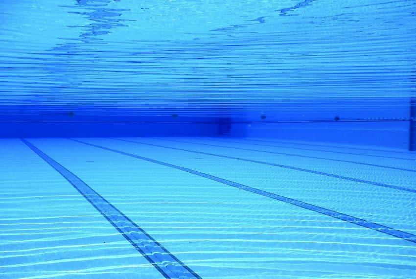 Imagem mostra fundo de piscina com água transparente.