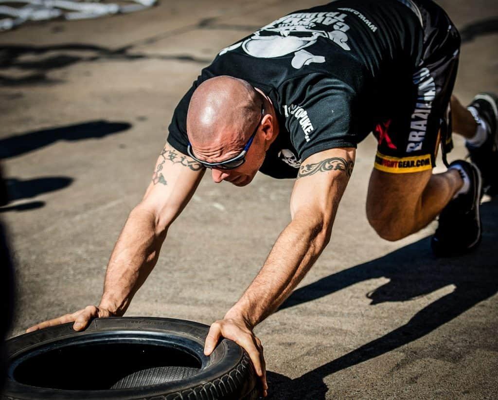 Imagem de um homem empurrando um pneu com as mãos