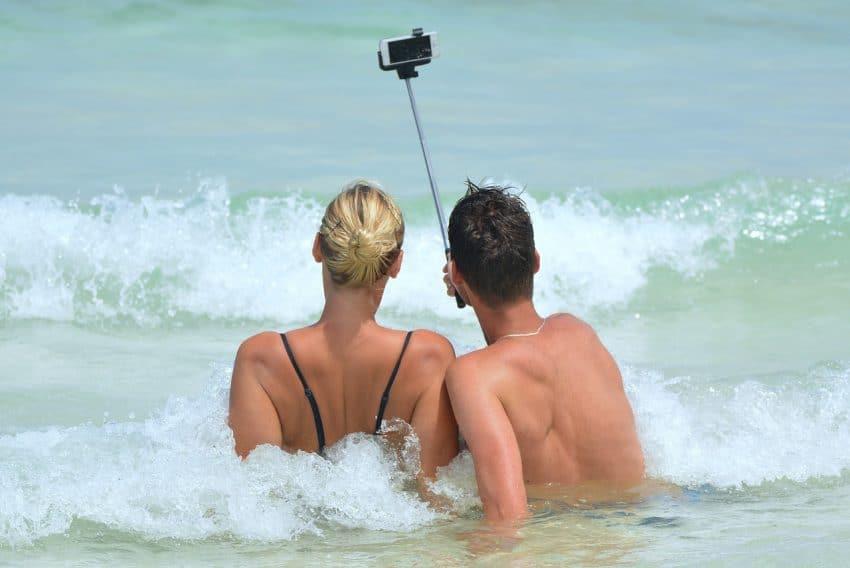 Casal de costas, no mar, tirando foto com pau de selfie.