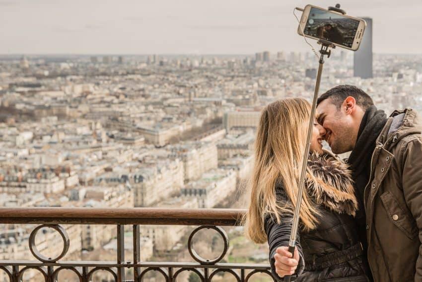 Imagem de um casal tirando foto com pau de selfie, prestes a beijar, no topo de um prédio. Ao fundo, a paisagem de uma cidade.