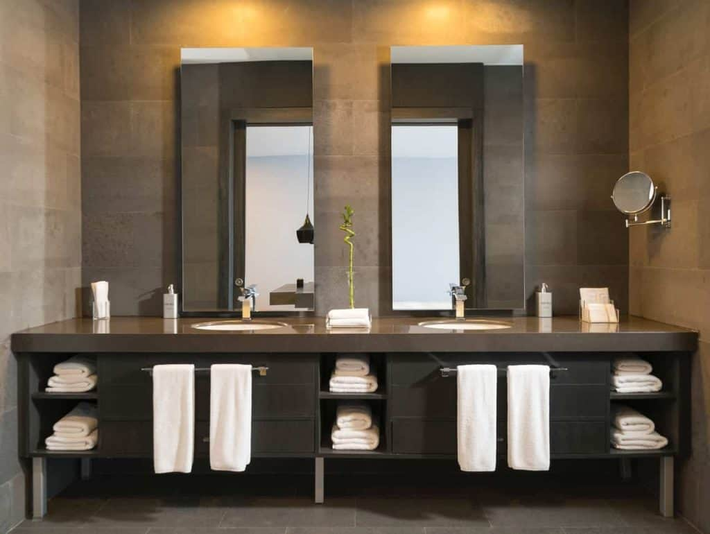Na foto um banheiro com paredes marrons, bancada com duas pias, dois espelhos e armários em tom de tabaco com toalhas brancas guardadas.