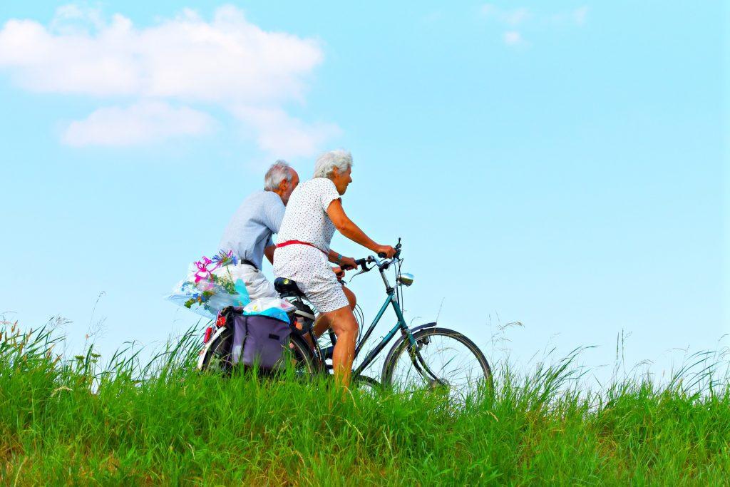Casal de idosos pedala em bicicletas com bolsas traseiras