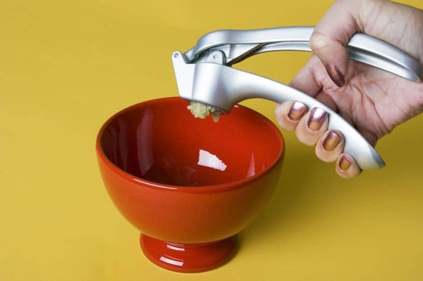 Imagem de pessoa espremendo alho.