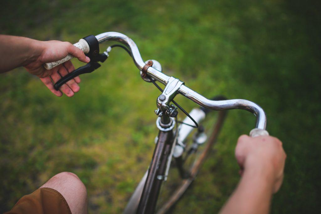 Imagem de pessoa acionando freios da bicicleta no guidão
