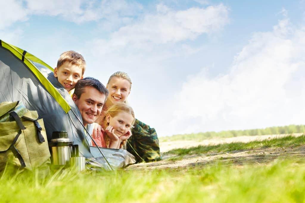 Família com a cabeça para fora da porta da barraca em uma linda paisagem