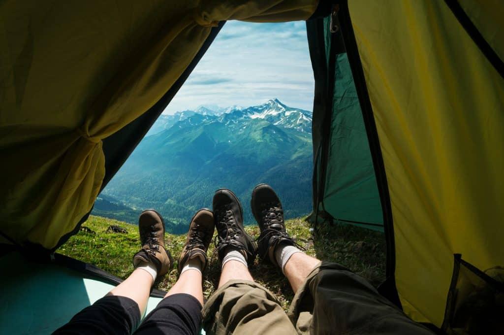 Pernas de uma casal para fora da barraca com linda vista de montanhas