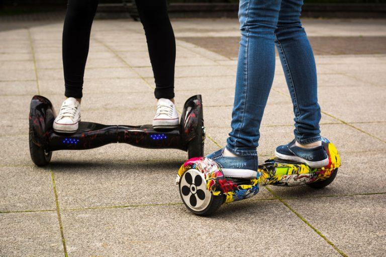 Imagem mostra da cintura para baixo duas pessoas andando de skate elétrico.