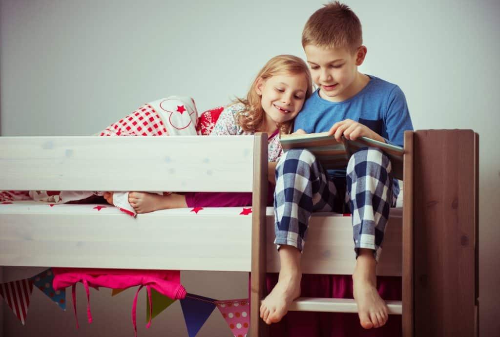 Menino e menina lendo em cima de uma cama superior de beliche.