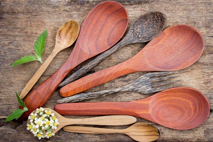 Na foto há sete colheres e um garfo de bambu dispostas sobre mesa de madeira com decoração de folhas e flores.
