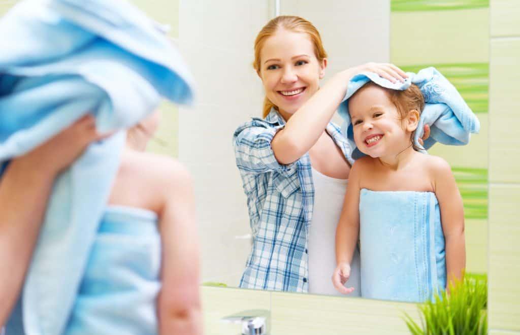 Na foto uma mulher secando os cabelos de uma criança de toalha em frente a um espelho dentro de um banheiro.