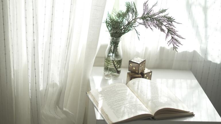 Eine weiße Gardine, auf einem kleinen Tisch befindet sich ein Buch sowie Deko